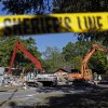Demolition experts watch as the home of Jeff Bush is destroyed Monday, March 4, 2013 in Seffner, Fla. A sinkhole opened up underneath the house late Thursday, Feb. 28, 2013, swallowing Bush, 37. The 20-foot-wide opening of the sinkhole was almost covered by the house, and rescuers said there were no signs of life since the hole opened Thursday night. (AP Photo/Scott Iskowitz)