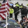 Photo - Police salute as a U.S. flag is raised at the finish line during a tribute in honor of the one year anniversary of the Boston Marathon bombings, Tuesday, April 15, 2014 in Boston.  AP Photo