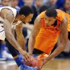 Kansas guard Naadir Tharpe, left, and Oklahoma State guard Marcus Smart, right, reach for a loose ball during the second half of an NCAA college basketball game at Allen Fieldhouse in Lawrence, Kan., Saturday, Jan. 18, 2014. Kansas defeated Oklahoma State 80-78. (AP Photo/Orlin Wagner)