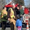 FILE - In this Dec. 14, 2012 file photo, a woman holding her children embraces a firefighter shortly after Adam Lanza opened fire, killing 26 people, including 20 children. While the people of Newtown do their best to cope with loss and preserve the memories of their loved ones, another class of residents is also finding it difficult to move on: the emergency responders who saw firsthand the terrible aftermath of last week\'s school shooting. (AP Photo/The Journal News, Frank Becerra Jr., File) NYC OUT, NO SALES, TV OUT, NEWSDAY OUT; MAGS OUT; MANDATORY CREDIT: THE JOURNAL NEWS, FRANK BECERRA JR.