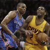 Cleveland Cavaliers\' Kyrie Irving, right, drives to the basket against Oklahoma City Thunder\'s Russell Westbrook (0) during the fourth quarter of an NBA basketball game on Saturday, Feb. 2, 2013, in Cleveland. Irving scored a team-high 35 points for the Cavaliers\' 115-110 win. (AP Photo/Tony Dejak) ORG XMIT: OHTD107