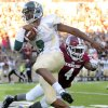 Photo - Cal Poly quarterback Chris Brown dodges New Mexico State's Winston Rose during an NCAA college football game Thursday, Aug. 28, 2014, in Las Cruces N.M. (AP Photo/Las Cruces Sun-News, Robin Zielinski)