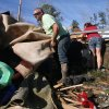 Chris Read pushes some carpeting away as he helps remove possessions from the family\'s tornado-damaged mobile home in Century, Fla., Tuesday, Feb. 16, 2016. (AP Photo/Michael Snyder)