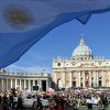 A flag from Argentina waves in the foreground as Pope Francis, bottom, is driven through the crowd prior to his inaugural Mass, in St. Peter\'s Square at the Vatican, Tuesday, March 19, 2013. Pope Francis thrilled tens of thousands of people on Tuesday gathered for his installation Mass, taking a long round-about through St. Peter\'s Square and getting out of his jeep to bless a disabled man in a wheelchair in the crowd. (AP Photo/Domenico Stinellis)