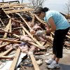 LaTisha Garcia finds a doll belonging to one of her daughters as she searches through the rubble of her tornado demolished home following Sunday\'s tornado in Moore, Okla., Thursday, May 23, 2013. (AP Photo/Sue Ogrocki)