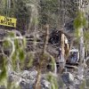 Searchers work with heavy equipment near the edge of a deadly mudslide, Wednesday, April 2, 2014, in Oso, Wash. Officials have so far confirmed the deaths of 29 people, although only 22 have been officially identified in information released Wednesday morning by the Snohomish County medical examiner\'s office. (AP Photo/Elaine Thompson)
