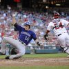Colorado Rockies\' Josh Rutledge (14) comes in to score on a single by DJ LeMahieu during the third inning of a baseball game against Washington Nationals catcher Kurt Suzuki (24), Friday, June 21, 2013, in Washington. (AP Photo/Nick Wass)
