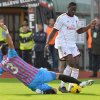 Photo - AC Milan forward Mario Balotelli, right, is tackled by Catania defender Nicolas Spolli, of Argentina, during the Serie A soccer match between Catania and AC Milan at the Angelo Massimino stadium in Catania, Italy, Sunday, Dec. 1, 2013. (AP Photo/Carmelo Imbesi)