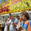 Photo - Greg and Lana Belcher of Marlow, Okla., eat jumbo corn dogs near the 14 Flags Plaza at the Oklahoma State Fair on Wednesday,  Sep. 18, 2013. Photo  by Jim Beckel, The Oklahoman.