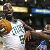 Photo - Boston Celtics forward Kevin Garnett (5) grabs a rebound against Orlando Magic forward Andrew Nicholson (44) during the first quarter of an NBA basketball game in Boston, Friday, Feb. 1, 2013. (AP Photo/Charles Krupa)