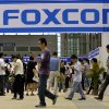 Photo -   FILE - In this file photo taken on May 22, 2010, visitors to a job fair walk past the Foxconn recruitment area in Shenzhen in south China's Guangdong province. The New York-based China Labor Watch has reported that 3,000 to 4,000 workers at the factory in Zhengzhou city went on strike Friday Oct. 5, 2012 over increased quality control demands and having to work during an extended national holiday. Foxconn Technology Group said Saturday that production at its central Chinese factory that makes Apple's iPhones was continuing without interruption, denying a labor watch group's report that thousands of workers at the plant had gone on strike. (AP Photo, File) CHINA OUT