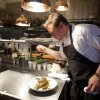Photo - n this photo taken Monday, Oct. 29, 2012, chef Tyler Florence puts a finishing touch to his fried chicken dish in the kitchen at his Wayfare Tavern in San Francisco. Baby food and fried chicken may well be the legacy for which Tyler Florence ultimately is best known. Which seems a bit crazy given his near ubiquity on the Food Network since its earliest days on air, his years of running the celebrity chef gauntlet, his many cookbooks, product lines and appearances.  (AP Photo/Eric Risberg)