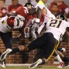 Oklahoma\'s Dejuan Miller (24) is brought down by Missouri\'s Trey Hobson (21) during their game Saturday in Norman.Photo by Chris Landsberger, The Oklahoman