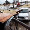 In pieces: Parts of a shopping center lie on a car near Northwest Expressway and Rockwell Avenue. PHOTO By John Clanton, The Oklahoman