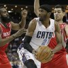 Charlotte Bobcats\' Hakim Warrick, center, looks to pass as he is trapped by Houston Rockets\' Carlos Delfino, right, and James Harden, left, during the first half of an NBA basketball game in Charlotte, N.C., Monday, Jan. 21, 2013. (AP Photo/Chuck Burton)