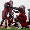 Photo - North Carolina State running backs Ben Grazen, left, and Tony Creecy participate in a drill during the team's first NCAA college football practice of the season in Raleigh, N.C., Saturday, Aug. 2, 2014. (AP Photo/Gerry Broome)