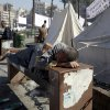 A man sleeps on a bench among others, some who have camped out in tents since last week, as opposition groups plan to gather for a major rally in Tahrir Square, Cairo, Egypt, Friday, Nov. 30, 2012. Islamists approved a draft constitution for Egypt early Friday without the participation of liberal and Christian members, seeking to pre-empt a court ruling that could dissolve their panel with a rushed, marathon vote that further inflames the conflict between the opposition and President Mohammed Morsi. (AP Photo/Thomas Hartwell)