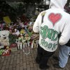 A Sandy Hook resident wears a handmade sweatshirt in support of his town while looking at a memorial to the Newtown shooting victims in the Sandy Hook village of Newtown, Conn., Saturday, Dec. 22, 2012. The funerals for the victims of the school shooting are wrapping up after a wrenching week of farewells. Twenty children and six adults were killed at Sandy Hook Elementary School on Dec. 14. Adam Lanza, the lone gunman, killed his mother before going on the rampage and then committed suicide. (AP Photo/Seth Wenig) ORG XMIT: CTSW106