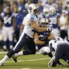 Photo - Indianapolis Colts' Donald Brown, center, is tackled by Tennessee Titans' Karl Klug (97) and George Wilson (21) during the first half of an NFL football game Sunday, Dec. 1, 2013, in Indianapolis. (AP Photo/Michael Conroy)