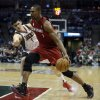 Miami Heat\'s Chris Bosh, right, drives past Milwaukee Bucks\' Ersan Ilyasova during the first half of Game 3 in their first-round NBA basketball playoff series on Thursday, April 25, 2013, in Milwaukee. (AP Photo/Morry Gash)