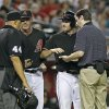Photo - Arizona Diamondbacks' A.J. Pollock, center right, shows his hand to home plate umpire Kerwin Danley (44) after being hit by Cincinnati Reds pitcher Johnny Cueto as manager Kirk Gibson, cenetr left, and assistant trainer Ryan DiPanfilo attend to Pollock during the eighth inning of a baseball game, Saturday, May 31, 2014, in Phoenix. The Reds defeated the Diamondbacks 5-0. (AP Photo/Ralph Freso)