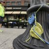 Photo - A passer-by walks past yellow and blue crocheted hearts that hang from a lamp post in front of the Forum restaurant near the finish line of the Boston Marathon Monday, April 14, 2014, in Boston. The restaurant was damaged after one of the bombs exploded in front of the building during the race April 15, 2013. (AP Photo/Steven Senne)