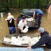 David Leslie, right, hauls sand bags with friends, Chad Riley, center, Taz Bowman, 18, left, and Tim O\'Neal, back, to the levee behind the Pleasant Ridge Mobile Home Park in Evansville, Ind. on Wednesday, April 27, 2011. Pigeon Creek snakes behind the area and is dangerously close to flowing over the levee. Most of the water in the park is from rain and from water that is coming back up through the storm drains.