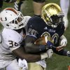 Notre Dame running back Cierre Wood (20) carries the ball and is tackled by Miami linebacker Gionni Paul during the second half of an NCAA college football game at Soldier Field, Saturday, Oct. 6, 2012, in Chicago. Notre Dame won 41-3. (AP Photo/Charles Rex Arbogast)
