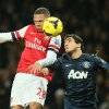 Photo - Arsenal's Kieran Gibbs, left, challenges for the ball as he out jumps Manchester United's Rafael during their English Premier League soccer match between Arsenal and Manchester United at the Emirates stadium in London, Wednesday, Feb. 12, 2014. (AP Photo/Alastair Grant)