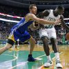 Photo - Golden State Warriors forward David Lee (10) reaches to defend against Boston Celtics power forward Brandon Bass (30) in the first half of an NBA basketball game in Boston, Wednesday, March 5, 2014. (AP Photo/Elise Amendola)