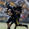 Missouri quarterback James Franklin, right, hands off to running back Kendial Lawrence as Lawrence runs for an 18-yard touchdown during the first half of an NCAA college football game against Oklahoma State Saturday, Oct. 22, 2011, in Columbia, Mo. (AP Photo/L.G. Patterson)