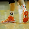 Oklahoma State sophomore guard Liz Donohoe\'s shoes are taped with the letters KB and MS to honor Kurt Budke and Miranda Serna, the two coaches killed in a plane crash one year ago on November 17, 2011. KT King/For the Tulsa World