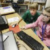 Colton Fuston, 8, a second-grader at Skyview Elementary, helps Caitlin Delaney, 9, a fourth-grader at Independence Elementary, learn to write computer code.