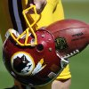 Photo - FILE - In this Sept. 23, 2012, file photo, Washington Redskins punter Sav Rocca carries a football in his helmet before an NFL football game against the Cincinnati Bengals in Landover, Md. The U.S. Patent Office ruled Wednesday, June 18, 2014, that the Washington Redskins nickname is