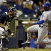 Photo - Chicago Cubs' Junior Lake slides safely past Milwaukee Brewers catcher Jonathan Lucroy during the seventh inning of a baseball game Tuesday, Sept. 17, 2013, in Milwaukee. (AP Photo/Morry Gash)