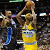 Denver Nuggets\' Corey Brewer (13) drives past Orlando Magic\'s Jameer Nelson (14) for a layup during the first quarter of an NBA basketball game, Wednesday, Jan. 9, 2013, in Denver. (AP Photo/Barry Gutierrez)