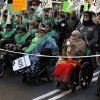 People march on wheelchairs as they carry banners reading,