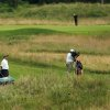 Photo - A group of people and a television camera follow Stanford's Patrick Rodgers, right, on the eighth hole during the first round of the NCAA college men's golf championship on Saturday, May 24, 2014, at Prairie Dunes Country Club in Hutchinson, Kan. (AP Photo/The Hutchinson News, Travis Morisse)