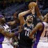 Minnesota Timberwolves\' Nikola Pekovic (14), of Montenegro, drives between Phoenix Suns\' Markieff Morris (11) and Jermaine O\'Neal during the first half of an NBA basketball game, Tuesday, Feb. 26, 2013, in Phoenix. (AP Photo/Matt York)