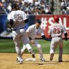 New York Yankees\' Derek Jeter, center, tags out Cincinnati Reds\' Skip Schumaker in a run-down during the eighth inning of the game at Yankee Stadium Sunday, July 20, 2014 in New York. (AP Photo/Seth Wenig)