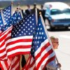 Photo - MILITARY / SOLDIER'S REMAINS / FORT SILL: Patriot Guard Riders hold American flags  near the hearse as they await the arrival of the plane carrying the soldier's casket.  The remains of U.S. Army SSgt. Travis Tompkins arrived in a flag-draped casket on a small jet that arrived at Henry Post Army Airfield  on Ft. Sill around 12 :45 Wednesday afternoon, March 23, 2011.  He died March 16 of wounds sustained in an attack the previous day when enemy forces attacked his unit in Afghanistan with a rocket-propelled grenade.  His funeral is scheduled for Friday.   Photo by Jim Beckel, The Oklahoman ORG XMIT: KOD