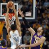 Photo - Denver Nuggets center JaVale McGee (34) dunks between Los Angeles Lakers center Dwight Howard (12) and forward Pau Gasol (16), of Spain, in the first quarter of an NBA basketball game in Denver, Wednesday, Dec. 26, 2012. (AP Photo/David Zalubowski)