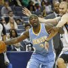 Photo - Denver Nuggets guard Ty Lawson (3) tries to get around Memphis Grizzlies guard Nick Calathes in the first half of an NBA basketball game Friday, April 4, 2014, in Memphis, Tenn. (AP Photo/Lance Murphey)