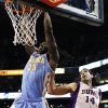 Denver Nuggets\' Kenneth Faried (35) dunks past Phoenix Suns\' Luis Scola (14), of Argentina, in the first half of an NBA basketball game, Monday, Nov. 12, 2012, in Phoenix. (AP Photo/Ross D. Franklin)