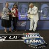 Wendell Scott Jr, right, Mable Scott, left, and Deborah Davis, center, pose for photos after Wendell Scott was named as one of five inductees into the NASCAR Hall of Fame class of 2015 during an announcement in Charlotte, N.C., Wednesday, May 21, 2014. (AP Photo/Chuck Burton)