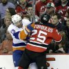Photo - New York Islanders' Colin McDonald (13) collides with New Jersey Devils Tom Kostopoulos (25) during the first period of an NHL hockey game Monday, April 1, 2013, in Newark, N.J. (AP Photo/Mel Evans)
