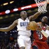 Photo - Miami Heat guard Dwyane Wade (3) goes up for a shot against Charlotte Bobcats forward Bismack Biyombo of the Democratic Republic of Congo, during the first half of an NBA basketball game, Monday, Feb. 4, 2013 in Miami. (AP Photo/Wilfredo Lee)