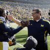 Michigan head coach Brady Hoke,right, greets quarterback Denard Robinson during a pre-game ceremony for seniors before an NCAA college football game against Iowa at Michigan Stadium in Ann Arbor, Mich., Saturday, Nov. 17, 2012. (AP Photo/Carlos Osorio)