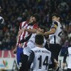 Photo - Atletico's Raul Garcia, centre, scores his goal in between Valencia players during a Spanish Copa del Rey soccer match between Atletico de Madrid and Valencia at the Vicente Calderon stadium in Madrid, Spain, Tuesday, Jan. 14, 2014. (AP Photo/Andres Kudacki)
