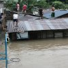 Filipinos move around roofs as floodwaters rise in suburban Quezon City, north of Manila, Philippines, on Tuesday Aug. 7, 2012. Relentless rains submerged half of the sprawling Philippine capital, triggered a landslide that killed eight people and sent emergency crews scrambling Tuesday to rescue and evacuate tens of thousands of residents. (AP Photo/Mike Alquinto)